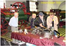 10h, Nogle museumsgæster diskuterer der flottet flymotormodeller - og i særdeleshed den 12 cylindrede Spitfiremotor, en model i 1:4, bygget af gunner Sørensen, som står i baggrunden og lytter til snakken!