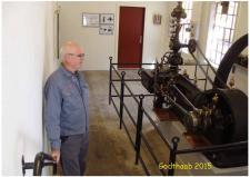 """6b, GODTHAAB HAMMERVÆRK indviede den 31. maj den """"genopstillede"""" Dampmaskine! På billedet viser museets mand Maskinen frem og lader den """"køre"""" ved hjælp et en elmotor! Dampmaskinen er udlånt af Danmarks Tekniske Museum i Helsingør. Maskinen er af samme type og størrelse, som den, der var i drift på Hammerværket. Effekt 45Hk – svinghjuls diameter 250cm – produceret år 1906 hos Frichs i Aarhus! Foto; Ks den 31. maj – GODTHAAB HAMMERVÆRK, Svenstrup ved Aalborg"""
